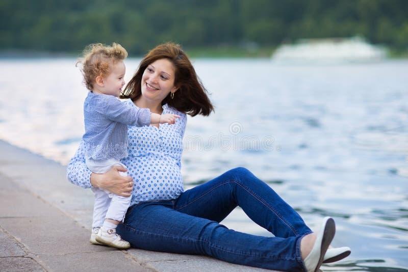 Mãe grávida dos jovens e sua filha pequena do bebê que relaxam na imagem de stock royalty free