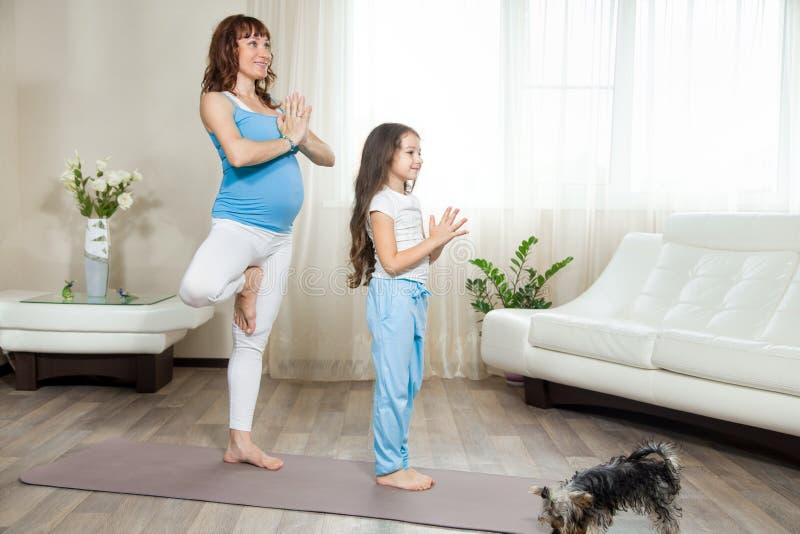 A mãe grávida e sua menina da criança que estão na árvore da ioga levantam em h imagens de stock