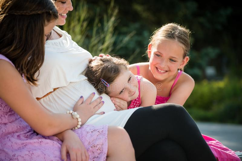 Mãe grávida feliz com as crianças exteriores na natureza do verão imagem de stock royalty free