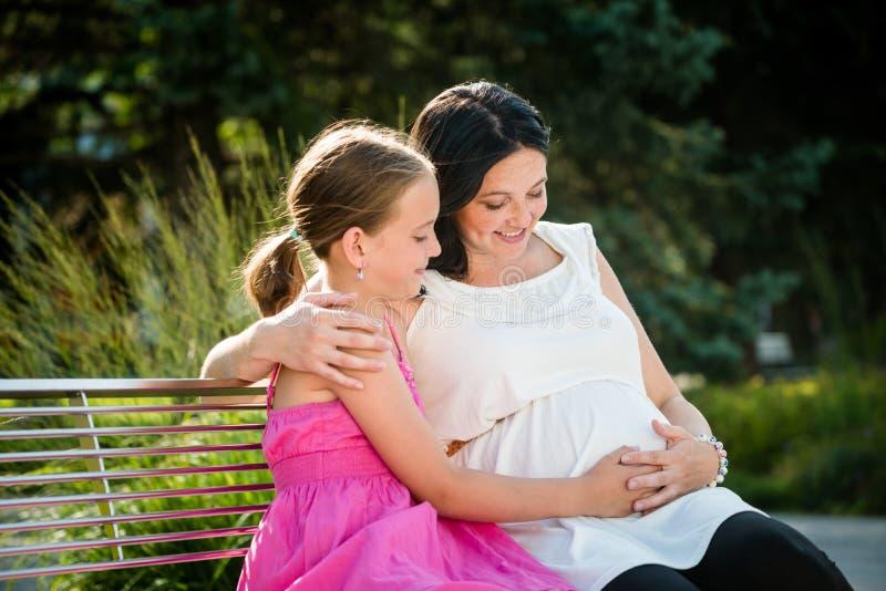 Mãe grávida que abraça sua filha bonito imagens de stock royalty free