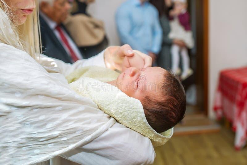 A mãe guarda a criança em suas mãos durante o rito do batismo foto de stock royalty free