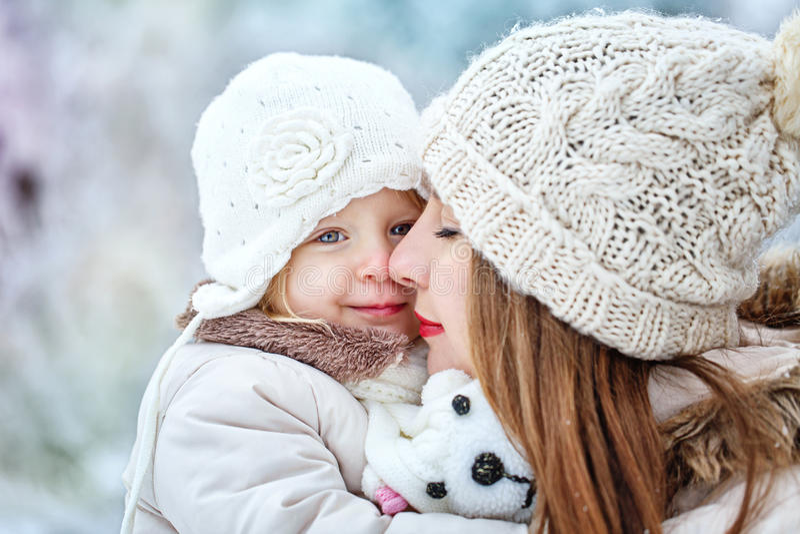A mãe guarda a filha nas mãos na floresta do inverno foto de stock royalty free