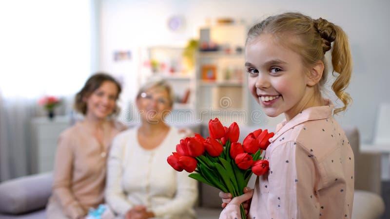 Mãe idosa e filha que olham a menina pequena que dá as tulipas, sorrindo na câmera fotografia de stock