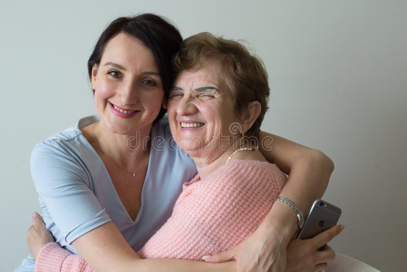 Mãe idosa que abraça a afeição adulta do conceito da filha foto de stock royalty free