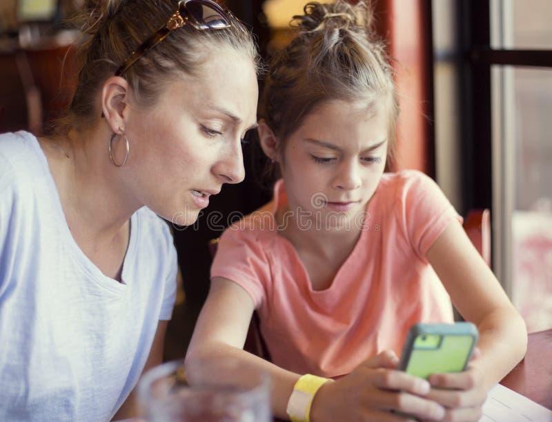 Mãe interessada que olha a criança que usa seu telefone esperto foto de stock