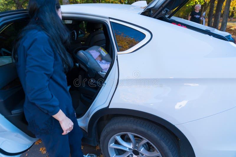 Mãe interessada que olha seu sono do bebê em um carro imagem de stock royalty free