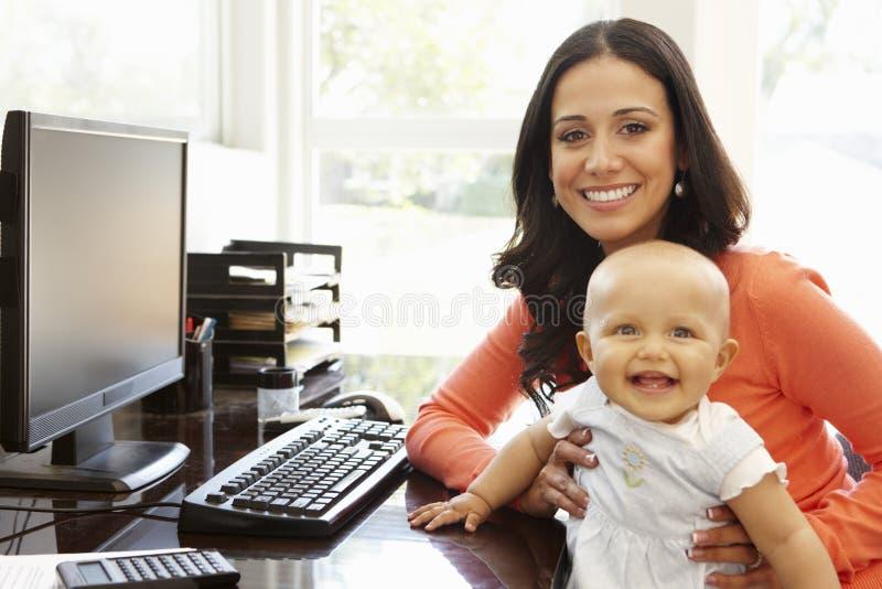 Mãe latino-americano com o bebê no escritório domiciliário de trabalho