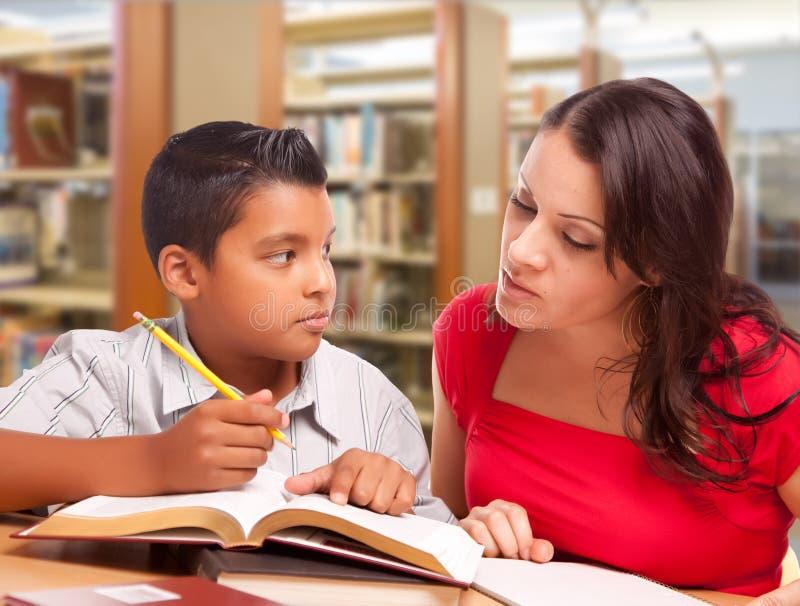 Mãe latino-americano e filho que estudam na biblioteca imagens de stock royalty free