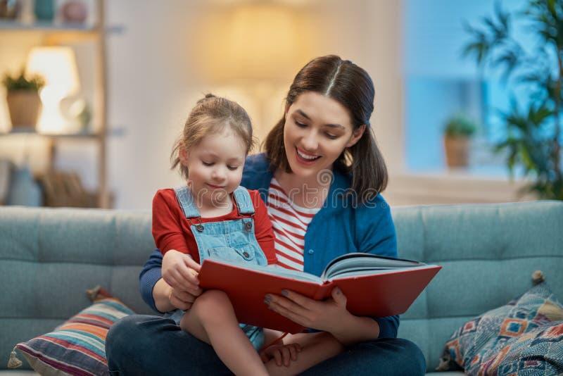 Mãe lendo um livro para filha foto de stock
