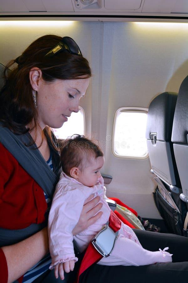 A mãe leva seu bebê infantil durante o voo fotos de stock