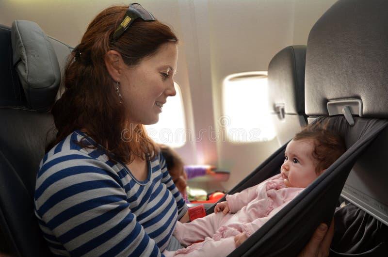 A mãe leva seu bebê infantil durante o voo fotografia de stock