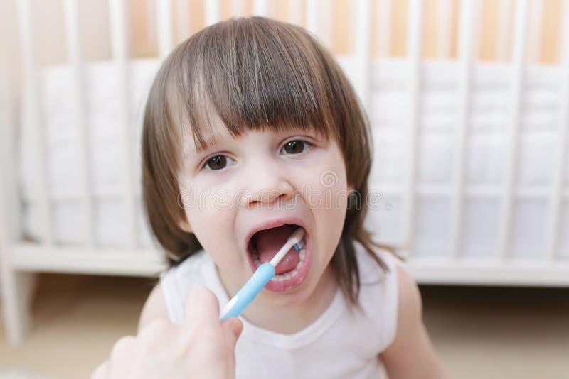 A mãe limpa os dentes seu filho fotos de stock royalty free