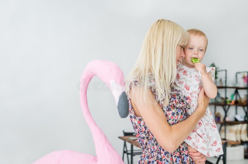 A mãe loura nova guarda a filha pequena nas mãos Bebê com um pirulito fotos de stock