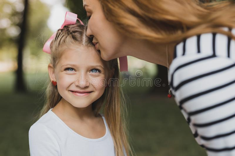 Mãe louro-de cabelo loving que beija sua menina pré-escolar bonito imagens de stock royalty free