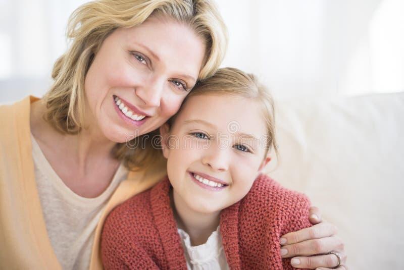 Mãe loving e filha que sorriem junto no sofá imagens de stock