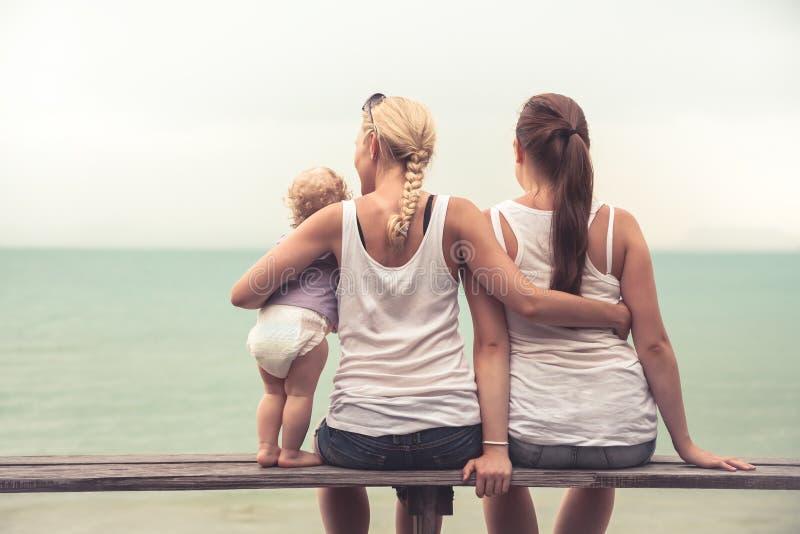 Mãe loving que abraça suas crianças que sentam-se no banco de madeira na praia tropical durante férias Eles que olham junto no di imagem de stock