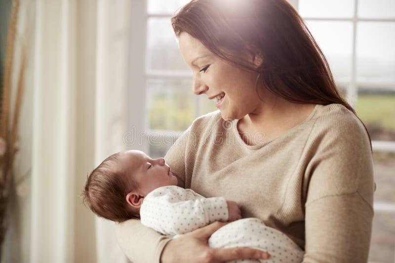 Mãe loving que afaga o bebê recém-nascido em casa fotografia de stock royalty free