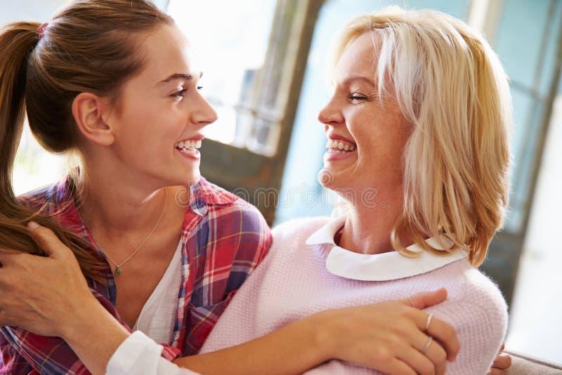 Mãe madura afetuosa com filha adulta em casa fotografia de stock