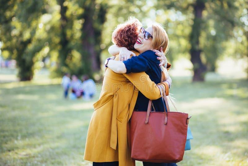 Mãe madura e filha adulta que abraçam no parque imagem de stock royalty free