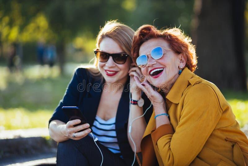 Mãe madura e filha adulta que escutam a música no smartphone fotografia de stock