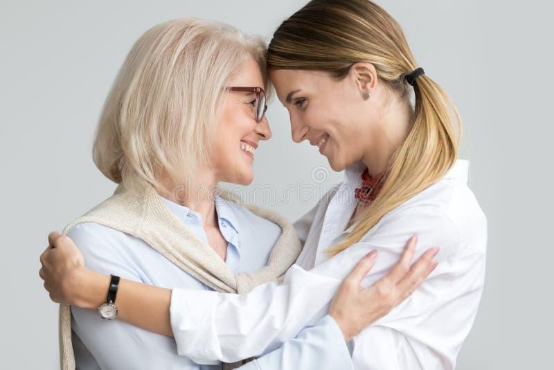 Mãe mais idosa envelhecida atrativa que abraça o touchi novo adulto da filha imagem de stock