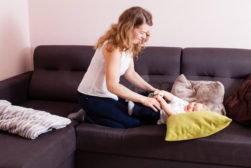 Mãe maravilhosa que passa o tempo com seu filho no sofá imagens de stock