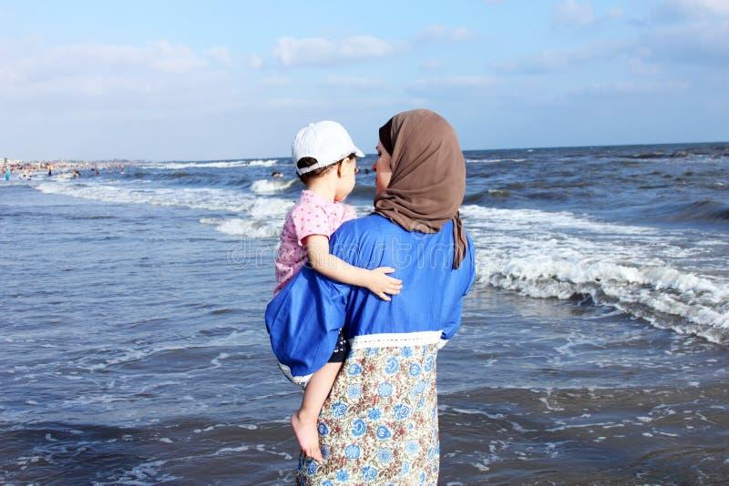 Mãe muçulmana egípcia árabe que guarda seu bebê na praia em Egito fotografia de stock royalty free