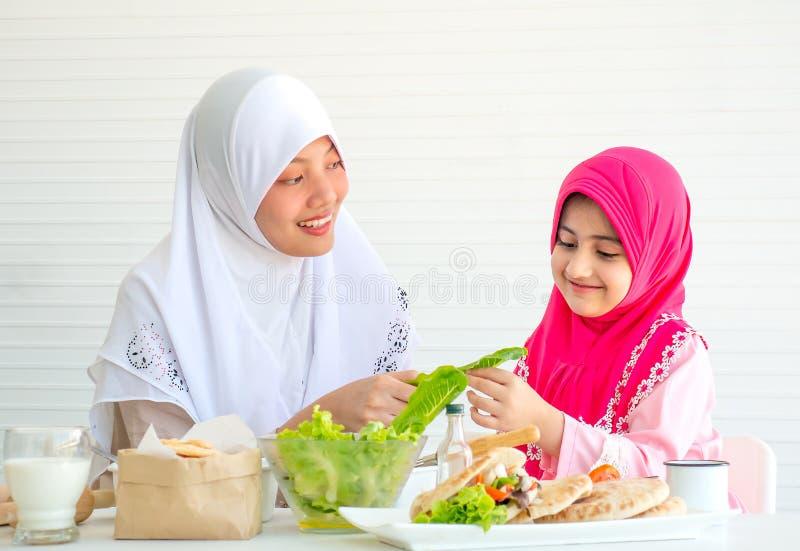 Mãe muçulmana para discutir e ensinar sobre o vegetal para o alimento a sua menina com fundo branco foto de stock