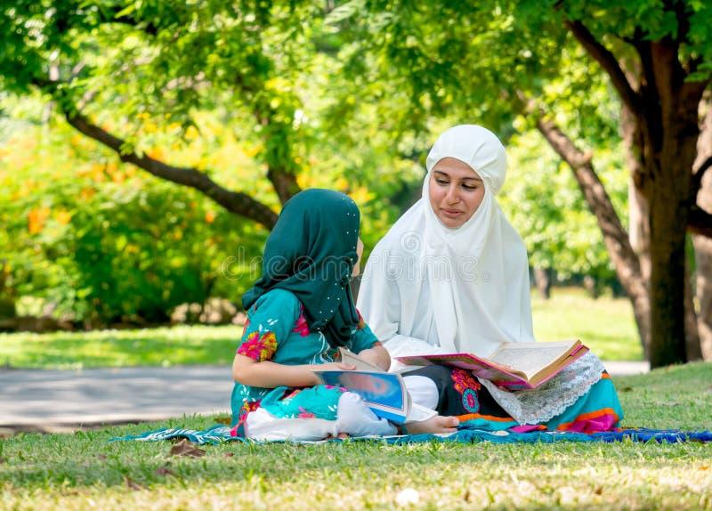 Mãe muçulmana para ensinar sua filha ler o livro de texto da religião para compreender a maneira de boa vida Ficam no jardim verd foto de stock