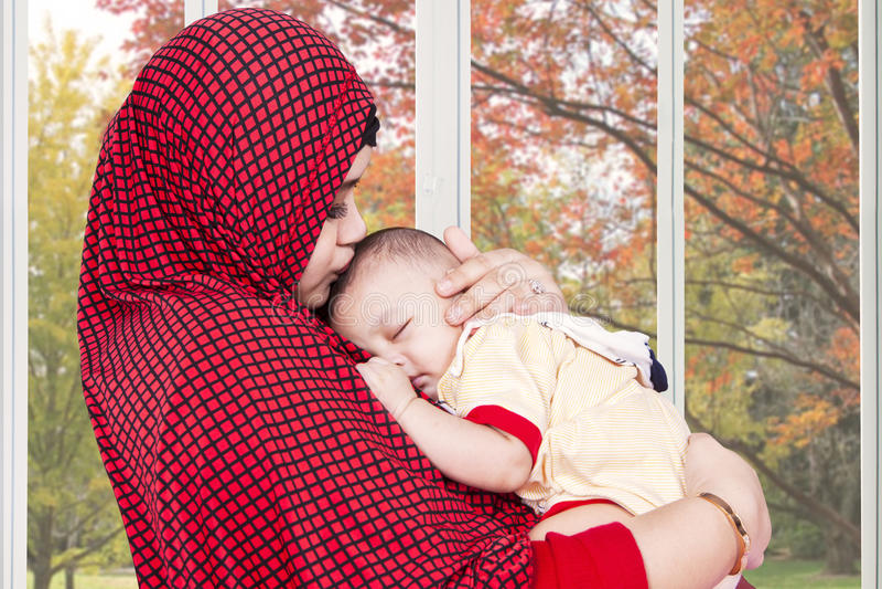 A mãe muçulmana tranquiliza seu bebê em casa fotos de stock royalty free