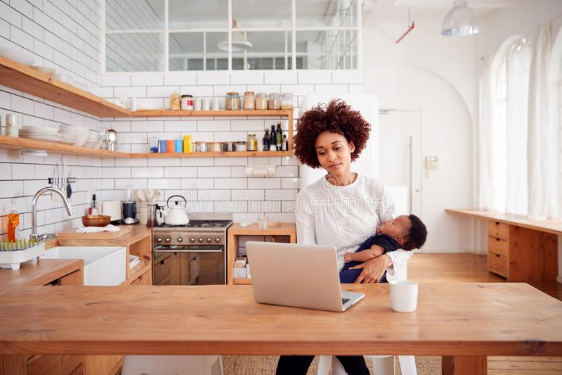 A mãe a multitarefas guarda o filho e trabalhos de sono do bebê no laptop na cozinha imagem de stock