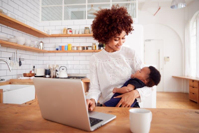 A mãe a multitarefas guarda o filho e trabalhos de sono do bebê no laptop na cozinha fotos de stock