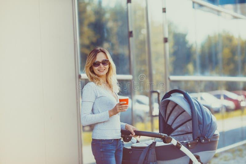 Mãe na moda que levanta com xícara de café e pram fotos de stock