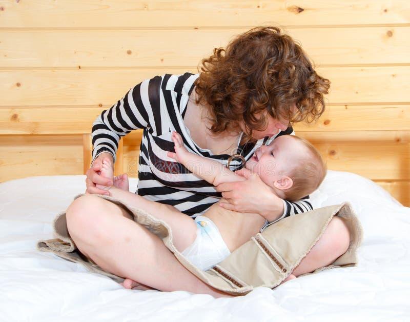A mãe na posição de lótus guarda seu bebê bonito fotografia de stock royalty free
