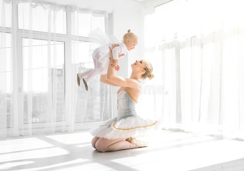 A mãe no equipamento do bailado que guarda sobre entrega a filha pequena imagens de stock