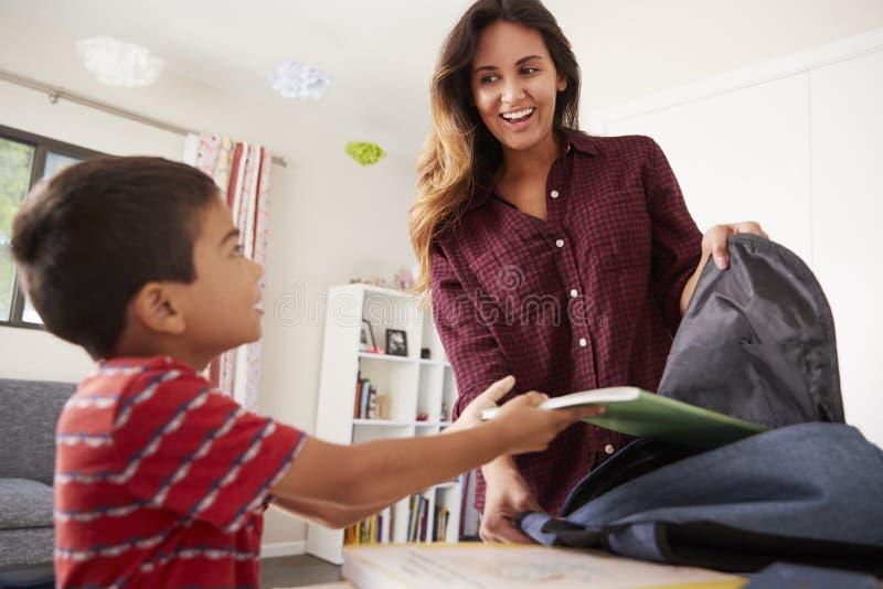Mãe no filho de ajuda do quarto para embalar o saco pronto para a escola fotografia de stock royalty free