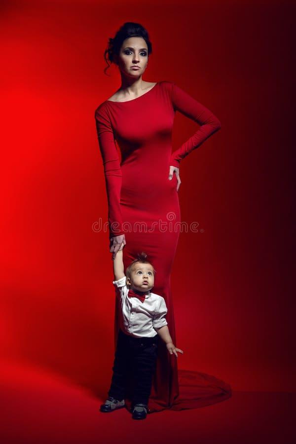 Mãe no vestido longo vermelho no estúdio imagens de stock royalty free