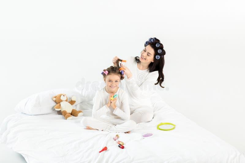 Mãe nos encrespadores que ondulam o cabelo à filha pequena feliz na cama fotos de stock