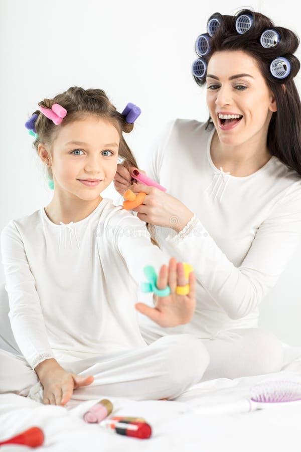 Mãe nos encrespadores que ondulam o cabelo à filha pequena feliz no branco fotos de stock royalty free