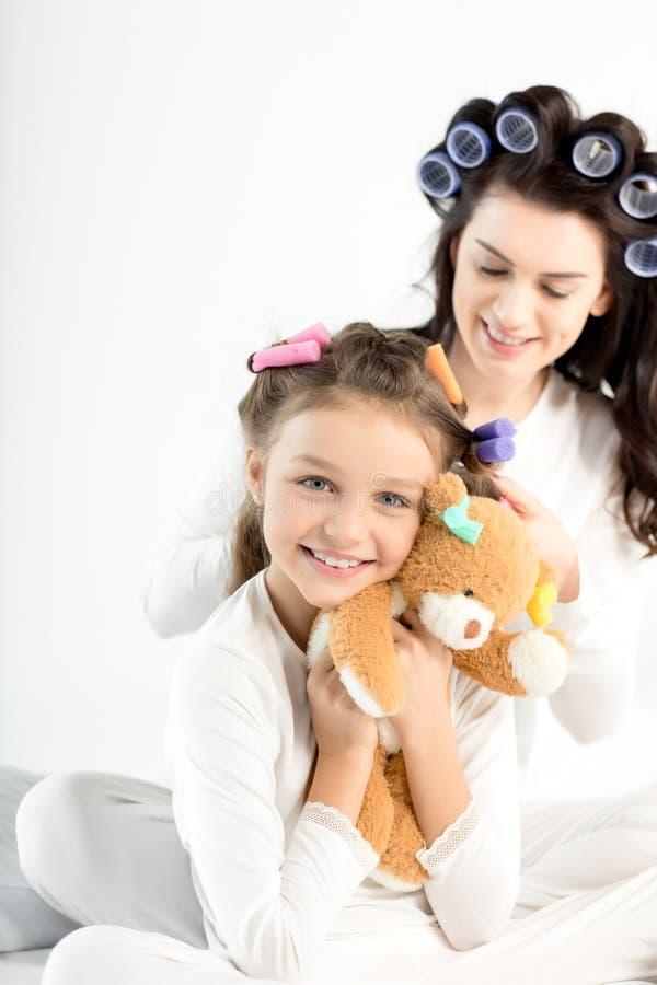 Mãe nos encrespadores que ondulam o cabelo à filha pequena feliz que abraça com urso de peluche imagens de stock