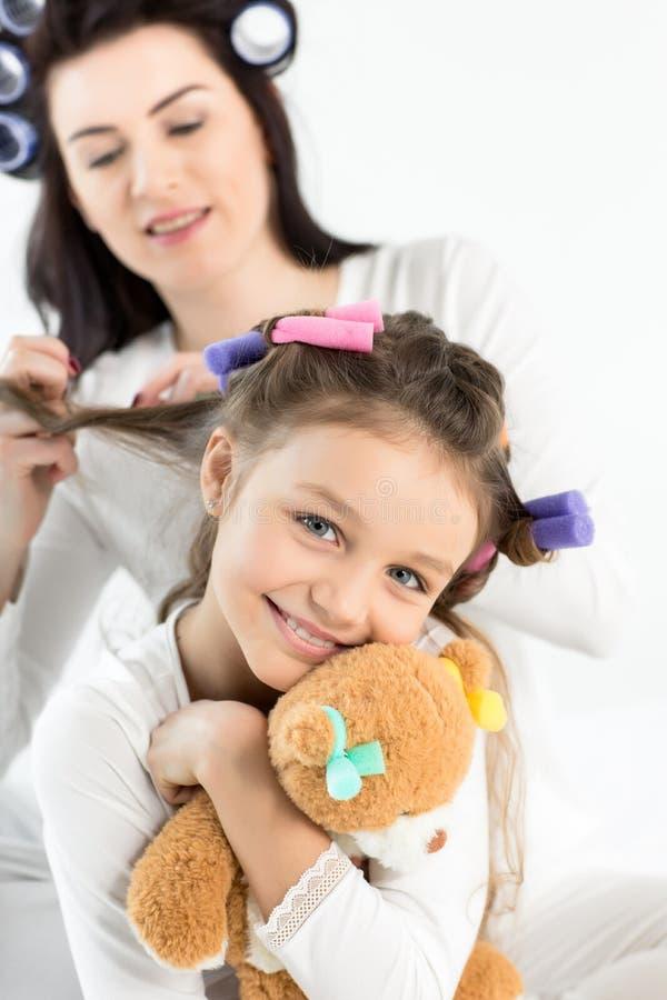 Mãe nos encrespadores que ondulam o cabelo à filha pequena feliz que abraça com urso de peluche fotografia de stock