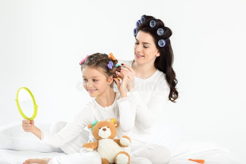 Mãe nos encrespadores que ondulam o cabelo à filha pequena feliz que olha o espelho à mão foto de stock