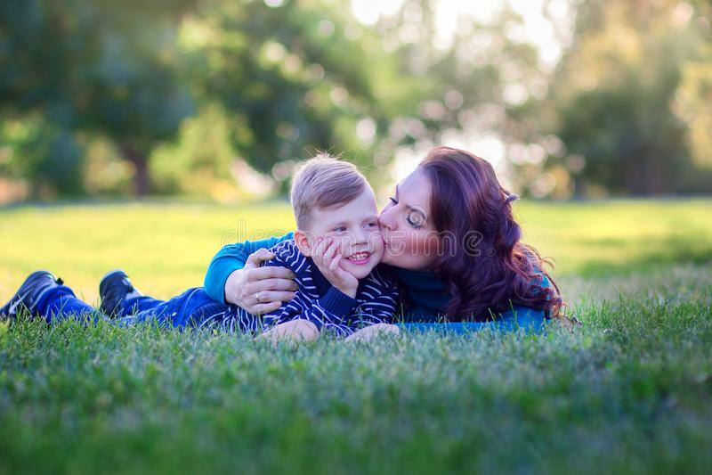 A mãe nova abraça e beija o filho que encontra-se em uma grama no parque fotos de stock