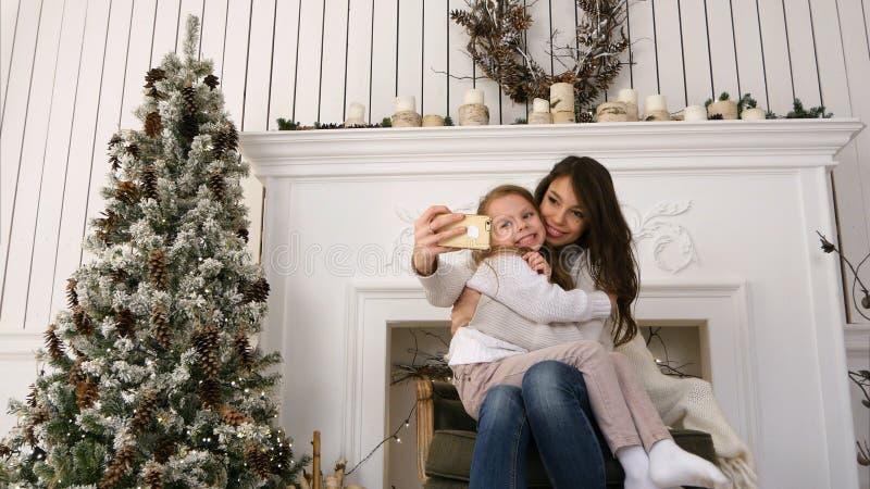 Mãe nova alegre e sua filha que fazem selfies cômicos do xmas e que mostram as línguas fotografia de stock