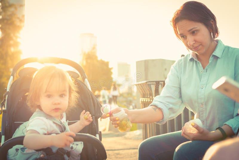 A mãe nova alimenta a menina da criança no transporte de bebê imagem de stock