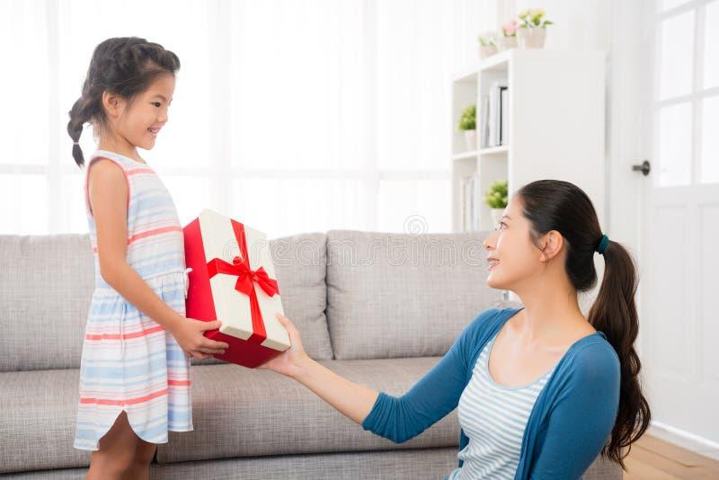 A mãe nova asiática aceita o presente da filha fotografia de stock royalty free