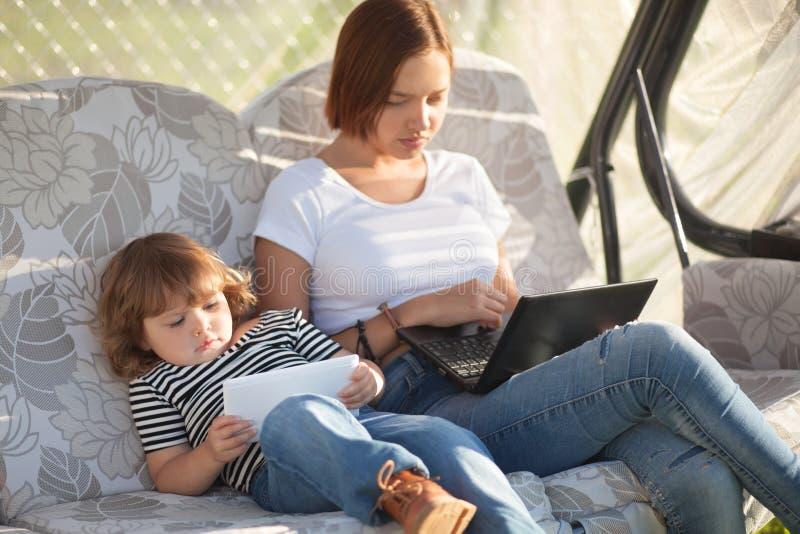 Mãe nova atrativa que usa o portátil, quando filha que joga a aba imagem de stock