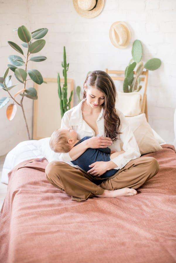 Mãe nova bonita com cabelo escuro longo em jogos confortáveis caseiros da roupa com seu filho novo em um quarto acolhedor foto de stock royalty free