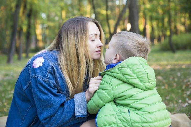 Mãe nova bonita com cabelo longo com o filho pequeno delicadamente tal fotografia de stock