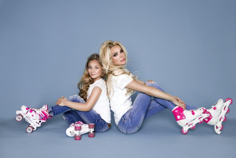 A mãe nova bonita com sua filha vestiu-se na roupa do verão e as calças de brim e os rolos fotografia de stock royalty free